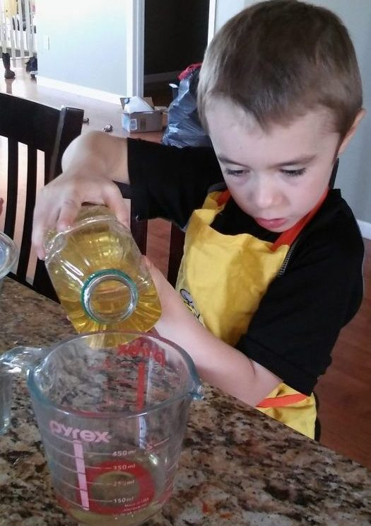 child practicing pouring skills cooking
